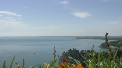 Pan and focus change from Duino castle ruins and sea to orange flowers Stock Footage