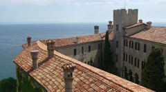 Duino castle over the rooftops view Stock Footage