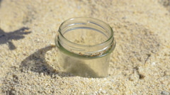 Hand of man throwing cigarette in a glass jar in the sand Stock Footage