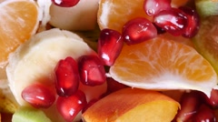Top view of a fruit salad with mandarin, oranges, kiwi, pomegranate seeds, figs Stock Footage