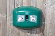 Green dog waste station under wooden background Stock Photos
