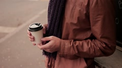 Young man with knitted scarf standing near the coffeeshop drinks coffee out of Stock Footage