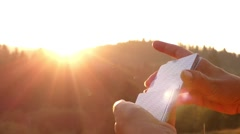 Hands Shuffle a Deck of Cards at Sunset in Rays of the Sun. Stock Footage