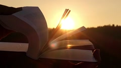 Silhouette of Book at Sunset. Turning Pages in Slow Motion in Sun Lights. Stock Footage