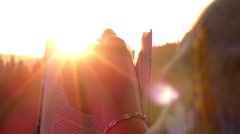 Slow Motion. Book in the Hands of Woman. Turning Pages at Sunset. Stock Footage