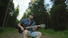 Man is playing at the electric guitar in forest Stock Footage