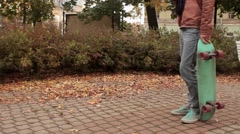 Young man with knitted scarf with skateboard sit down on bench in autumn park Stock Footage