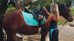 Woman Saddles up His Horse Near the Stables Stock Footage