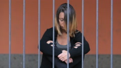 Imprisoned depressed girl sitting cross-legged Stock Footage