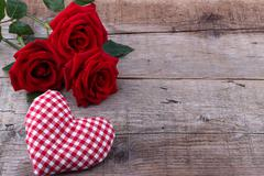 Hearts and a bouquet of red roses on wooden board, Valentines Day background Stock Photos