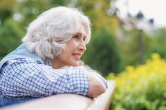 Dreamful old lady relaxing outdoors Stock Photos