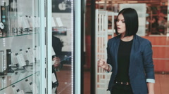 Shopping. Young brunette woman passes near the shop window of accessories for Stock Footage