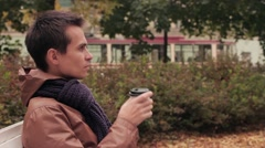 Young man with knitted scarf sitting on bench in autumn park drinks coffee out Stock Footage