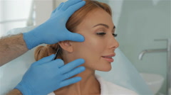 Cosmetologist stretches the skin on client's cheek Stock Footage