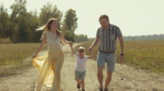 Beautiful mother and handsome father running in the field holding their child Stock Footage