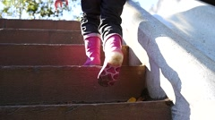 Legs in boots - a child climbs the stairs in slow motion Stock Footage