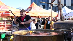 Sofia Bulgaria healthy food street festival chef stirs a huge vat of cookin soup Stock Footage