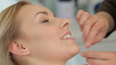Masseur massages client's face from chin till ear Stock Footage