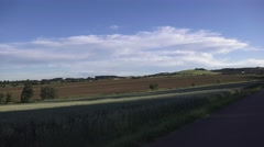 Driving pass large field in Europe Stock Footage