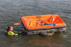 Rescue worker showing life raft in harbor Urk, the Netherlands Stock Photos