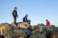 Three friends have fun climbing on a rock Stock Photos