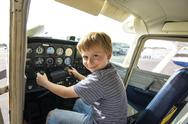 Boy has fun sitting in an aircraft at the pilots seat Stock Photos