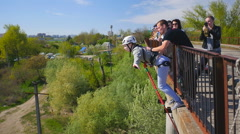 The girl uncertainly with the help of instructors jumping from the bridge Stock Footage