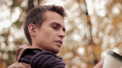 Young man in brown jacket and knitted scarf in autumn park drinks coffee out of Stock Footage