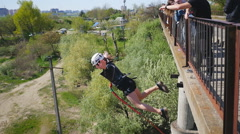 Girl jump from the bridge facing forward with the help of instructor Stock Footage
