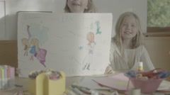 A pair of little blonde girls show off their drawing and explain what it means. Stock Footage