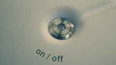 Metallic button on-off  is recessed on the white surface of the device Stock Footage
