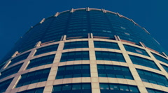 The wall of glass and concrete skyscraper circular shape reflects the blue sky Stock Footage