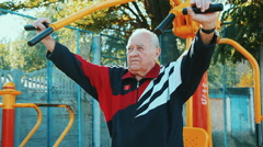 Elderly man exercising with fitness equipment in public outdoor gym Stock Footage