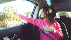 Pretty romantic woman in a car enjoying the wind, hand playing in the air, thumb Stock Footage