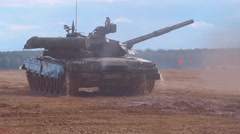 T-90 tanks are driving in a row on a ground road, stir up dust Stock Footage