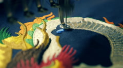 Sewing machine embroider beautiful colorful pattern on blue cloth Stock Footage