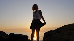 Girl smiling and enjoy a moment in sunrise sun over the sea where birds fly Stock Footage