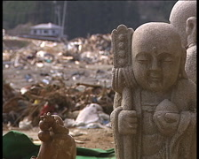 Budda statue on the ruins of Minami Sanriku town after great Japan tsunami Stock Footage