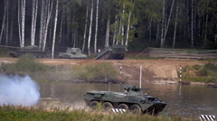 Armoured military vehicles going to swim across the river, and btr moving Stock Footage