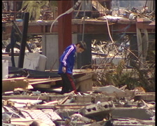 Young japanese boy looking for home stuff on the site of his destroyed house. Stock Footage