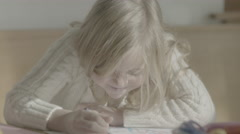 A pair of young sisters sit at the table, carefully coloring inside the lines. Stock Footage