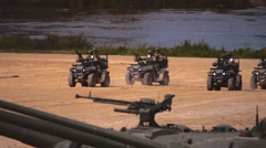 Military ATVs with armed soldiers moving on a dirt road on military exercises Stock Footage