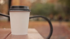 White paper cup with hot drink in autumn city park close up with shot defocused Stock Footage