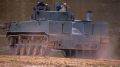 Armored military BMP and soldiers on the board, moving to the river and stopped Stock Footage
