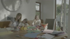 Two girls draw with their mom then get bored and run outside Stock Footage