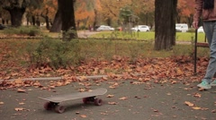 Skater while picking up skateboard continue walking slow motion Stock Footage