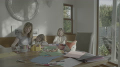 Mother and her daughters work on a family art project in a suburban home. Stock Footage