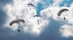 Military parachutists lands on a background of clouds and blue sky Stock Footage