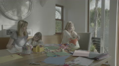 Child cleans up art supplies while her mother sits, holding her younger sister. Stock Footage