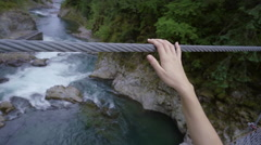 Closeup Of Woman's Hands Lightly Touching Suspension Bridge As She Walks Across Stock Footage